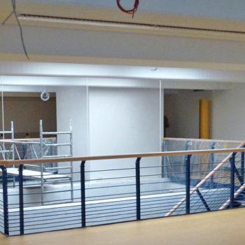 Galeriegeländer mit Doppelpfosten und waagerechten Füllstäben mit Übergang in ein Treppengeländer